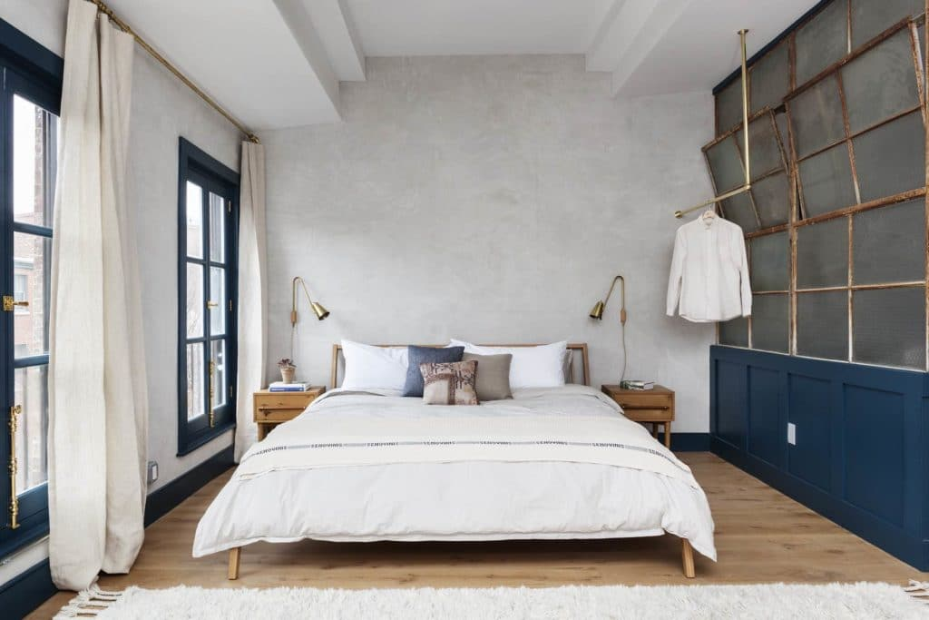 King bed flooded with light from floor to ceiling windows and brass task lighting on either side with clothes hanging from an exposed brass rod next to a reclaimed factory window divider