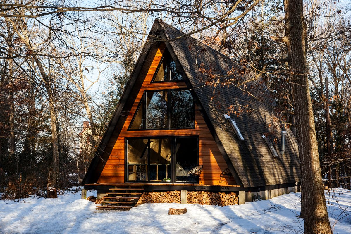 An Aframe cabin in the woods with snow on the ground and firewood under the front porch