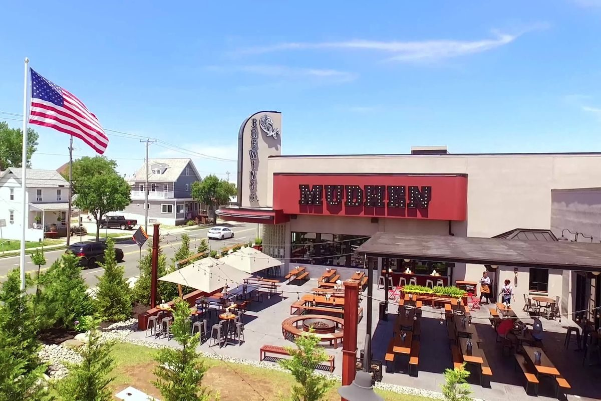 Drone shot of the outdoor picnic tables and fire pits with awnings, shades and string lights at Mudhen Brewery in Wildwood NJ