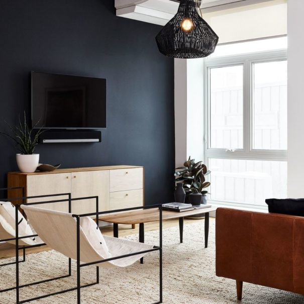 The Living room in the Baller Jawn at Lokal Hotel Fishtown with leather couch, two sling lounge chairs, a woven overhead light and locally handmade wooden coffee table and credenza under smart tv and sonos speaker
