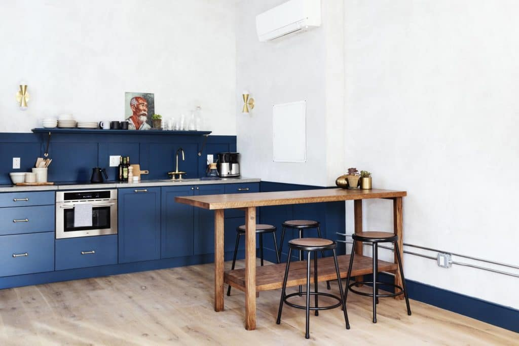 A blue kitchen in the Louisa suite at Lokal Hotel Old City with brass hardware and open shelf with a handmade wooden island and table with four stools