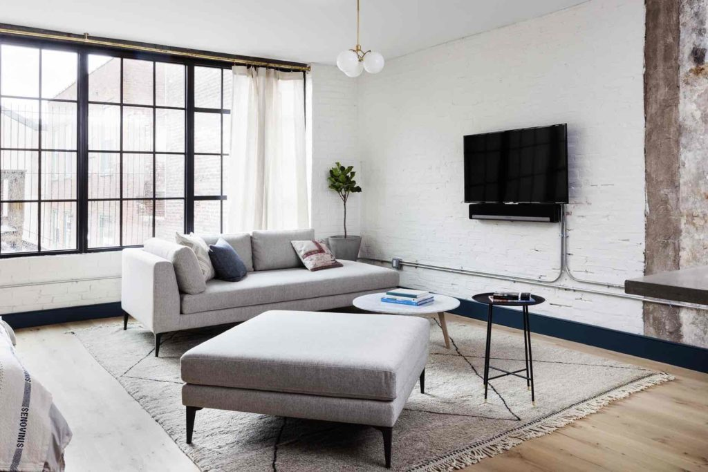 Living area of an apartment suite at Lokal Hotel Old City with couch and ottoman on top of vintage rug with tv on the wall with a sonos speaker and large factory windows flooding the room with light