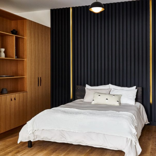 Queen bed with casper mattress and parachute linens with floor to ceiling black headboard with integrated led lighting and white oak shelving and wardrobe