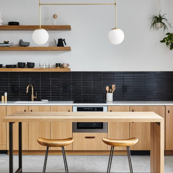 Efficiency apartment style kitchen in lokal hotel fishtown with sleek scandinavian color scheme of white, black and white oak and black steel