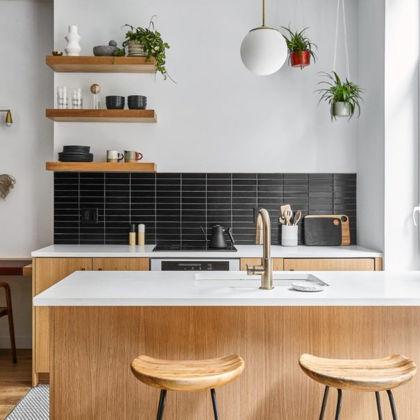 white oak kitchen with island and white quartz countertops floating shelves and brass light fixture with hanging plants in the corner and two stools behind the island and ADA sitting desk to the left