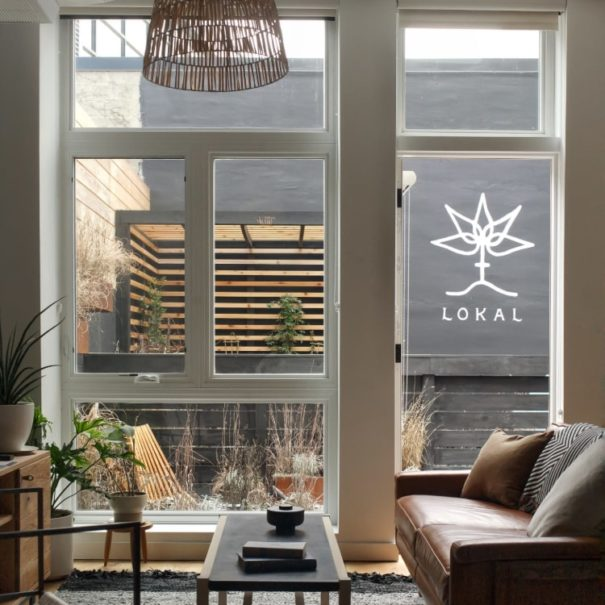 View of the Garden Jawn living room at Lokal Hotel Fishtown looking over the garden through the windows in the back of the property with seating, trellis and logo painted on the back wall