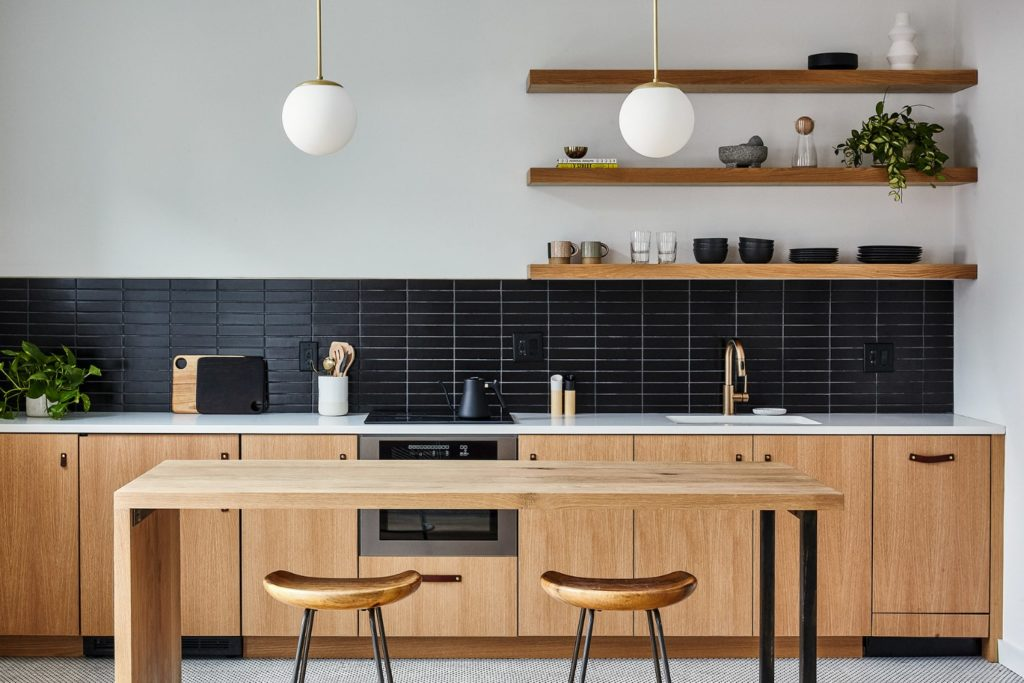 An efficient studio apartment hotel kitchen with white oak built in appliances a black tile backsplash and floating shelves with steel and wood island and stools and brass pendant lights